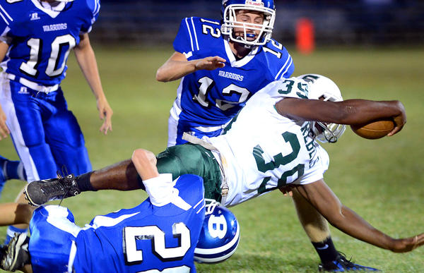 South Hagerstown's Isiaha Smith (39) is brought down by Boonsboro's Chad Cowden, top right, and Ethan Foster, bottom, in the second quarte Friday night at Boonsboro.