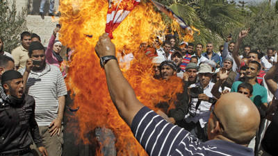 An Islamist Jordanian protester burn the U.S. flag near the U.S. embassy in Amman, Jordan, Friday, Sept. 14, 2012, as part of widespread anger across the Muslim world about a film ridiculing Islam's Prophet Muhammad.