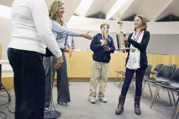Debra Cradduck, from second left, congratulates Palm Crest Elementary's Solenn Matuska, far right, after winning the district's spelling bee contest in February. Palm Crest received top scores in a survey released last week.