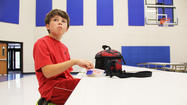 Jacob Tobin, a fifth-grader at C.C. Lee Elementary school, eats his packed lunch at the opposite end of the table from other children who bring their lunches from home.