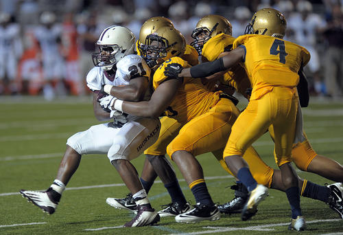 St. Thomas Aquinas defenders stop Don Bosco Prep running back Elijah Ibitokun-Hanks during the second half of their game.