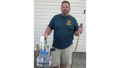 Bill Price holds equipment used in his Petoskey-based business, Sunshine Window Cleaning and Pressure Washing.