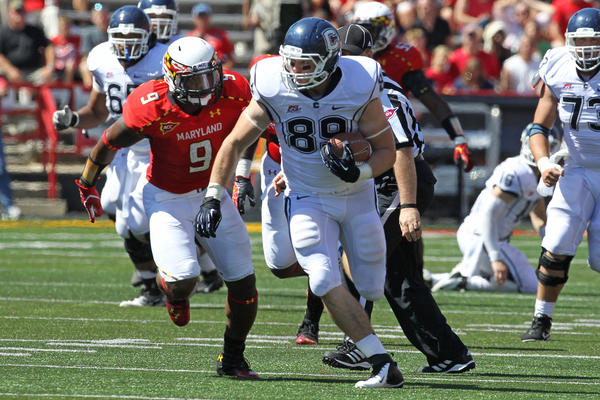 Connecticut Huskies tight end James Horan (88) runs past Maryland Terrapins linebacker Demetrius Harstfield (9) at Byrd Stadium.