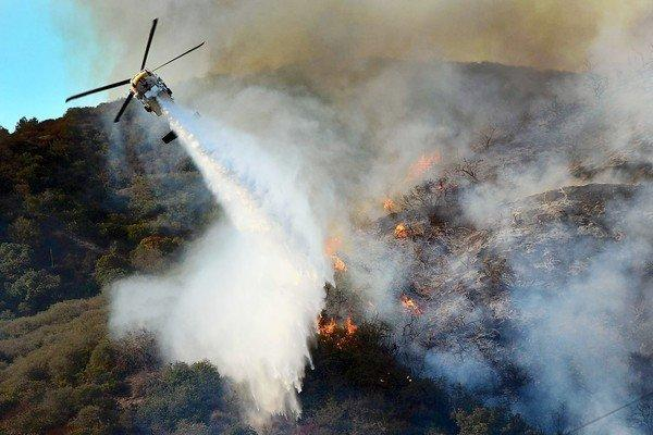 An L.A. County helicopter drops water in a battle against a rapidly moving brush fire in the Sepulveda Pass.