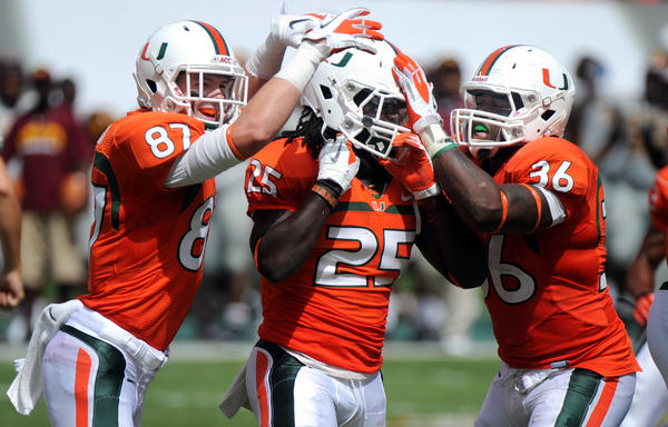 Dallas Crawford of the University of Miami gets congratulated by teammates Gionni Paul (right) and Garrett Kidd after intercepting a fake punt in the fourth quarter against Bethune-Cookman.