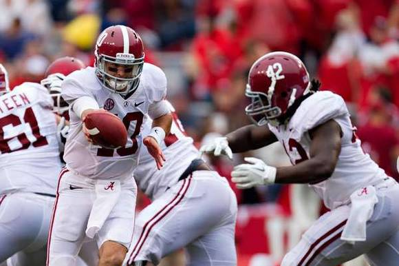 AJ McCarron #10 fakes a handoff to Eddie Lacy #42 of the Alabama Crimson Tide