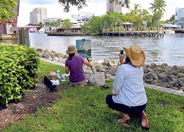 "Terry Noonan takes a picture of her friend, Holly Sutter, during a timed art competition along the New River in downtown Fort Lauderdale on Saturday. Artists had two hours to complete their work during the Quick Draw Riverwalk ""paint out""."