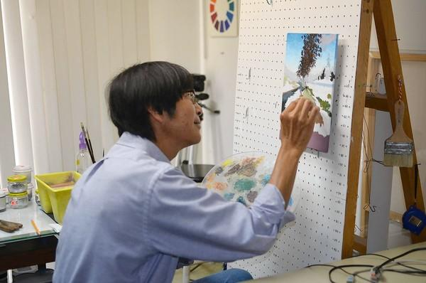 "Max Yamada works on an original painting, ""Back Bay Walking,"" at his Newport Beach home studio on Friday."