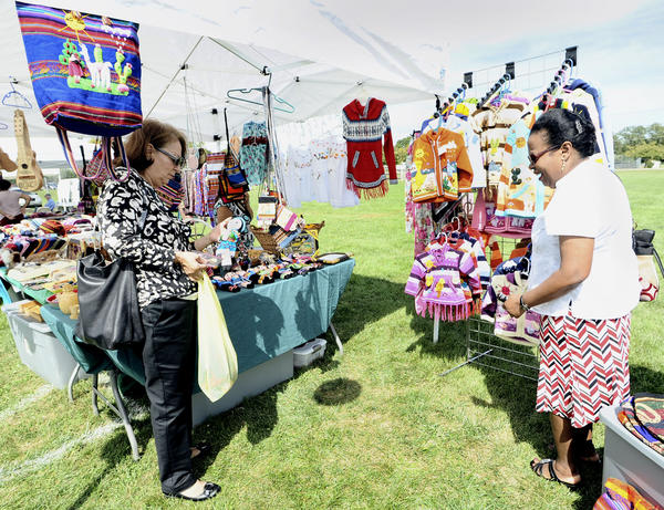 Romana Rodriguez, left, and Jocelyn Villaman look over a vendor's selections Sunday at the sixth annual Hagerstown Hispanic Festival at Fairgrounds Park.