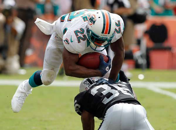 Miami Dolphins running back Reggie Bush (22) breaks a tackle by Oakland Raiders cornerback Shawntae Spencer (36) for a touchdown in the third quarter at Sun Life Stadium.