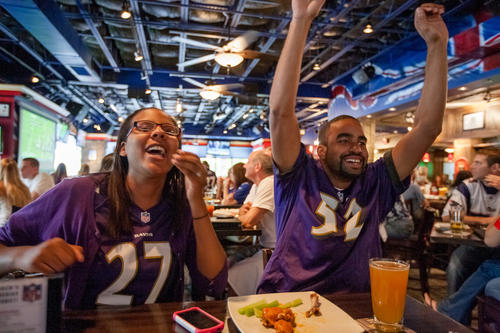 Derek Burks, of Columbia, and his wife, Kenisha, cheer as the Ravens make a big play during the first quarter.