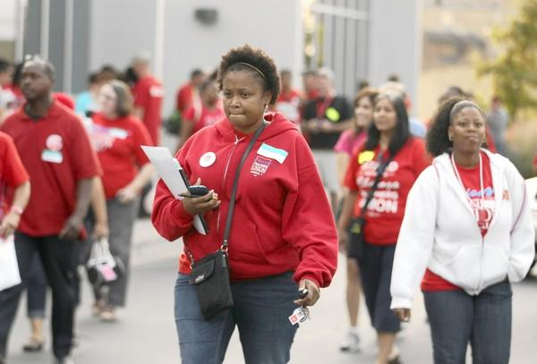 Members of the Chicago Teachers Union ruling body leave the International Union of Operating Engineers hall Sunday after deciding to continue the teachers strike, now in its second week. The earliest school could start is Wednesday.