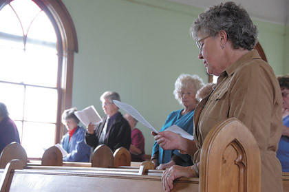 Evie Pond, right, sings a hymn during the annual service at Powell Church. More than 30 people came to the special service Sunday at the church in Pioneer Village in Ipswich.