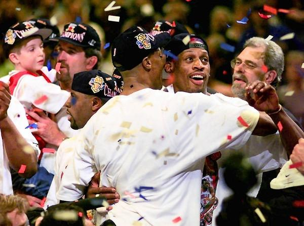 The Chicago Bulls Scottie Pippen hugs teammate Dennis Rodman, facing camera, after the Bulls beat the Utah Jazz to win their sixth championship in eight years in Salt Lake City in 1998. Coach Phil Jackson is at rear, left.