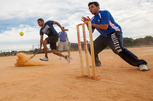 Arun Murugesan, of Columbia (left), runs to safely score a run for the CricITers as Rushiraj Brahmbhatt, of Columbia, prepares to catch the ball during a play.