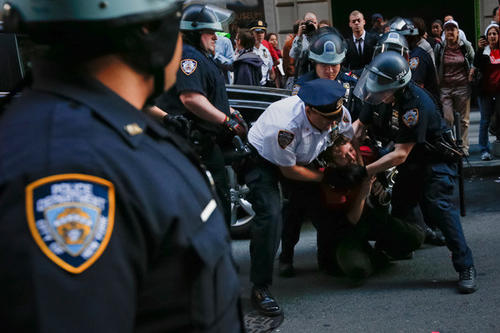 An Occupy Wall Street activist is arrested by policemen on the one-year anniversary of the movement in New York.