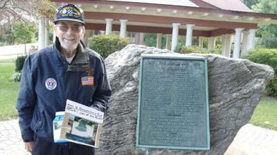 Gordon Wiitanen stands by the World War I memorial in Petoskey's Mineral Well Park, which he hopes to see moved to Pennsylvania Park downtown.