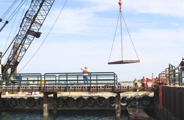 A crew from the crane barge Manitowoc in cooperation with the U.S. Army Corps of Engineers lifts a grid from the walkway to begin fixing the cement at the base of the Pine River Channel pier in Charlevoix. Work on the project is expected to be complete by Nov. 1.