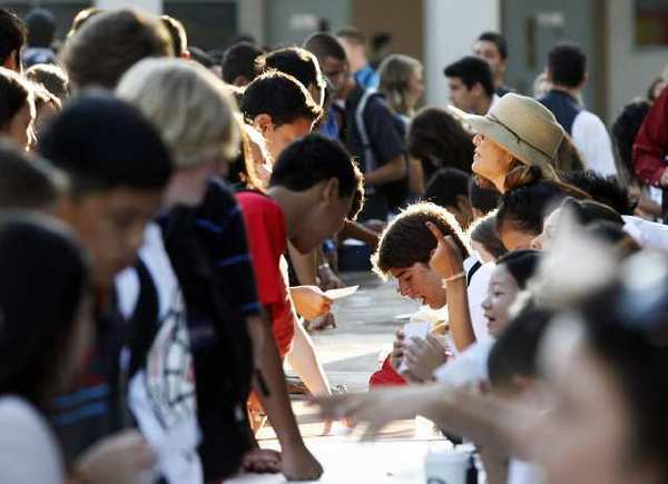 A long line of alphabetcally organized tables doled out the schedules for students on the first day of school at John Burroughs High School in Burbank on Monday, August 13, 2012.