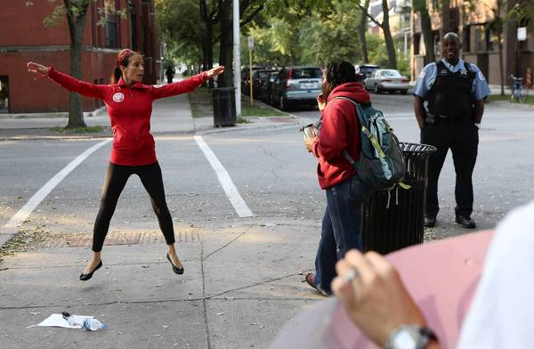 Ray Elementary School kindergarten teacher Jamie Madsen does jumping jacks while she and fellow teachers stand outside the school in the Hyde Park neighborhood of Chicago. She was doing the morning fitness that the school does every day to boost brain function.