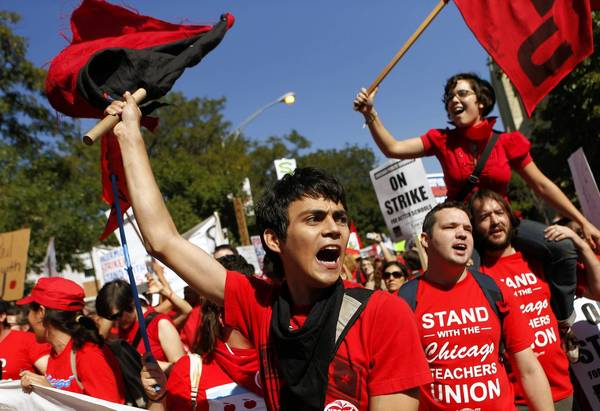 Freddy Martinez (left) and Teresa Veramendi (top) participate in a Chicago Teachers Union march after a rally Saturday.