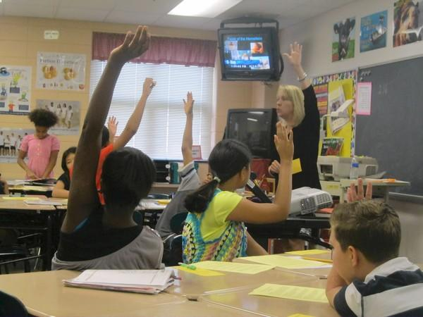 Students in Sharon Marbury's sixth-grade class at Ellicott Mills Middle School raise their hands to answer questions from Cathy Smith, a representative from the Grassroots Crisis Center.