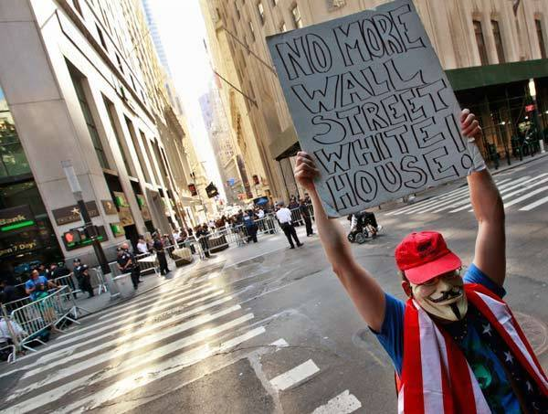 An Occupy Wall Street activist stands at the foot of Wall St. in the financial district during the one-year anniversary of the movement in New York.
