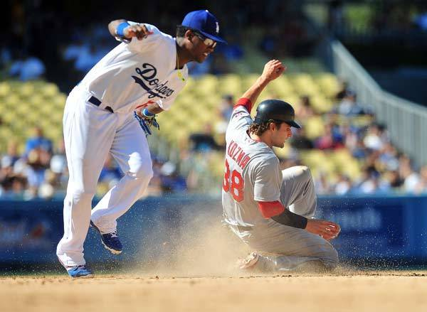 St. Louis Cardinals shortstop Pete Kozma (38) steals second against the tag of Los Angeles Dodgers shortstop Hanley Ramirez (13) in the seventh inning at Dodger Stadium.