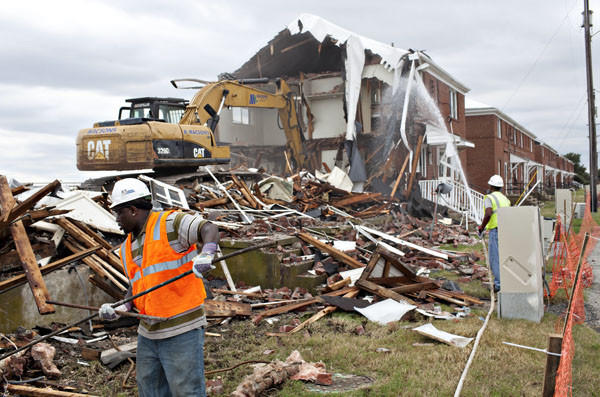 Matthew Paul, left, a worker of Macsons Demolition and Environmental Services, collects copper pipes to recycle as the first building of The Wherry Quarter at Fort Monroe is demolished in Hampton on Monday, September 17, 2012. Thirty one buildings will be torn down next couple of months.