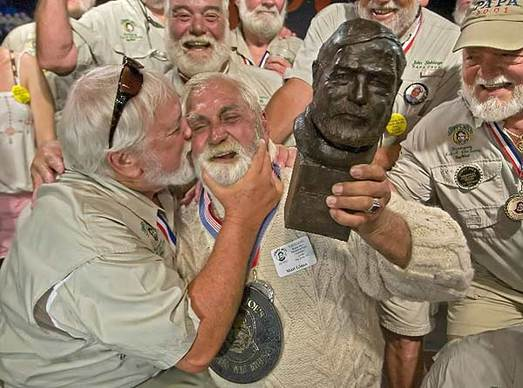 """2009 Ernest Hemingway look-alike winner David Douglas (L) kisses Matt Gineo (C) after Gineo was selected the 2011 """"Papa"""" Hemingway Look-Alike Contest winner at Sloppy Joe's Bar in Key West, Florida July 23, 2011. It was the 12th try for Gineo, a 64-year-old Jensen Beach, Florida biomedical engineer who beat 120 other entrants. The contest was a highlight event of the six-day Hemingway Days festival that ends July 24. Picture taken July 23, 2011."""