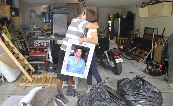 Kyoko Zaldivar, right, holds a picture of her son Alex Zaldivar who was shot and killed as she hugs Alfonso Campos, left, the father of Brienna and Remington Campos who were also shot in the head but survived. The Zaldivar and Campos families describe how the two were terrorized by by home invaders May 10, a day before they were scheduled to testify against two men who broke into the same home and tied them up and robbed them in May.