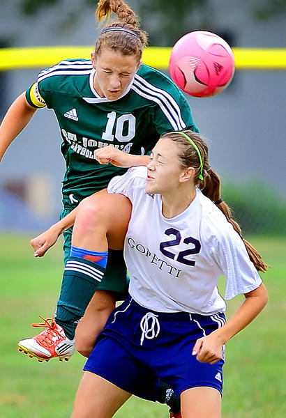 St. John's Catholic Prep's Amelia Clark (10) heads the ball above St. Maria Goretti's Alexis Barone (22) during Monday's girls soccer game at Goretti.