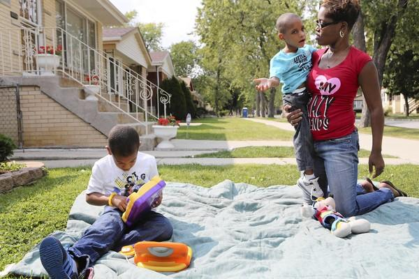 Tameeka Chalmers holds her son Antwuan Staton Jr., 5, right, and as nephew Emjay Hardy, 6, (all cq) sits at her Far South Side home Monday on the of Chicago, Monday, September 17, 2012. Antwuan Staton has cerebral palsy and is missing out on school therapy during the teachers strike.