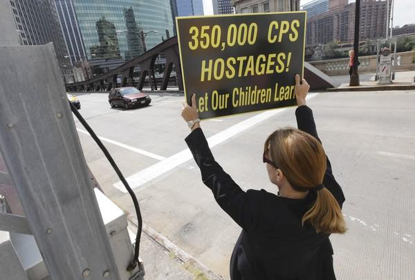 Laura Mondrowski joins a group of 18 parents of Chicago Public Schools students to protest the teachers strike Monday outside the Merchandise Mart, where the teachers union is headquartered.