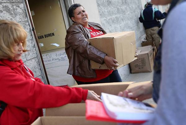 American Federation of Teachers organizer Samantha Jordan struggles to carry a box informational papers to hand outside schools at strike headquarters at 1642 W. Van Buren in Chicago.