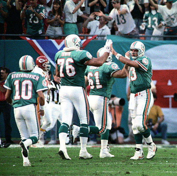 <b>12/31/1994</b><br></br> Miami Dolphins v Kansas City Chiefs Wildcard Playoff Game at Joe Robbie Stadium (now Sun Life Stadium) Dolphins quarterback Dan Marino is congratulated by teammates Tim Ruddy (61) and Tim Irwin (76) after throwing a touchdown pass to tie the game at 17 in the second quarter.