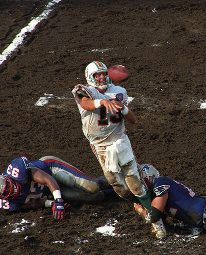<b>09/04/1994</b><br></br> Miami Dolphins v. New England Patriots at Joe Robbie Stadium (now Sun Life Stadium). In the third quarter of the game, Dolphins quarterback Dan Marino is hit by New England Patriots Defensive Tackle, Tim Goad (72) and Defensive End, Mike Pitts (93) after he rushed a pass which was caught by Irving Fryar for a first down. Dolphins won the season opener 39 - 35.
