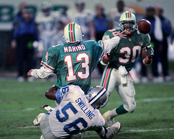 <b>12/25/1994</b><br></br> Miami Dolphins v Detroit Lions at Joe Robbie Stadium (now Sun Life Stadium) Dolphin's quarterback Dan Marino gets off a low pass to running back Bernie Parmalee (30) to avoid a sack by Lion's linebacker Pat Swilling (56) with 1:31 left in the second quarter. The Dolphins clinched the AFC East title with this 27-20 Christmas Day win over the Lions.