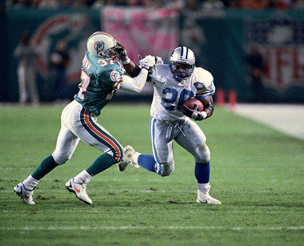 <b>12/25/1994</b><br></br> Miami Dolphins v Detroit Lions at Joe Robbie Stadium (now Sun Life Stadium) With 3:29 left in the third quarter, Lions superstar running back, Barry Sanders (20) gives a stiff-arm to Dolphin's corner back J.B. Brown.