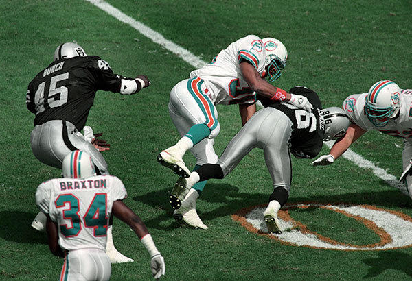 <b>10/16/1994</b><br></br> Miami Dolphins v Los Angeles Raiders at Joe Robbie Stadium (now Sun Life Stadium)  Dolphin's running back Bernie Parmalee takes down Raider's wide receiver Raghib Ismail in the second quarter.