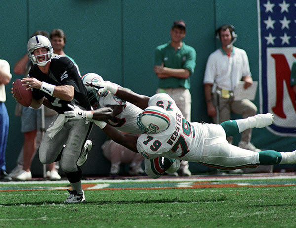 <b>10/16/1994</b><br></br> Miami Dolphins v Los Angeles Raiders at Joe Robbie Stadium (now Sun Life Stadium) Raider's quarterback Jeff Hostetler is pressured by Dolphin's defensive tackle Larry Webster (79) and defensive end Marco Coleman (90).