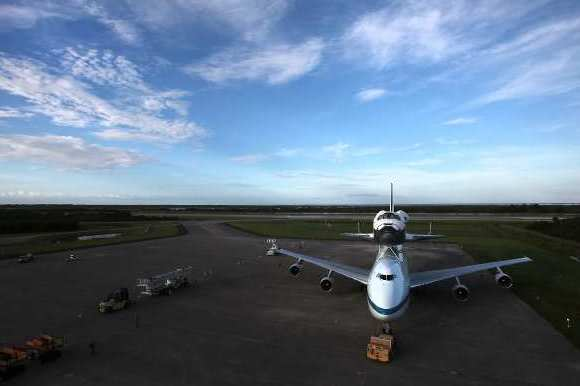 The space shuttle Endeavour sits atop a modified Boeing 747 on the apron at the Kennedy Space Center.