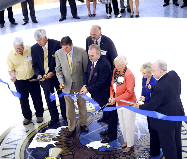 Participating in Tuesday's ribbon cutting at the new finance center for American Public University System in Charles Town, W.Va., are, from left, Jefferson County Commissioner Dale Manuel; Ranson (W.Va.) Mayor David Hamill; U.S. Sen. Joe Manchin, D-W.Va.; Sen. Herb Snyder, D-Jefferson/Berkeley; Wallace Boston, president of American Public University System; Charles Town (W.Va.) Mayor Peggy Smith; Del. Tiffany Lawrence, D-Jefferson; and Harry Wilkins, chief financial officer of American Public University System.