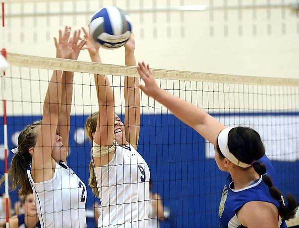 Boonsboro's Shelby Wallace (2) and Meredith Craig (9) block a kill attempt by Clear Spring's Kristen Mellott, right, in the third set of Tuesday night's MVAL Antietam volleyball match in Boonsboro.