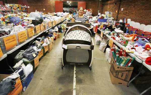 Elizabeth Barajas, of Van Nuys, rolls a portable crib to the checkout counter at the LA Kids Consignment sale in Burbank on Tuesday, where 625 consignors contributed 95,000 children's toys, clothes, games, strollers and a lot more.