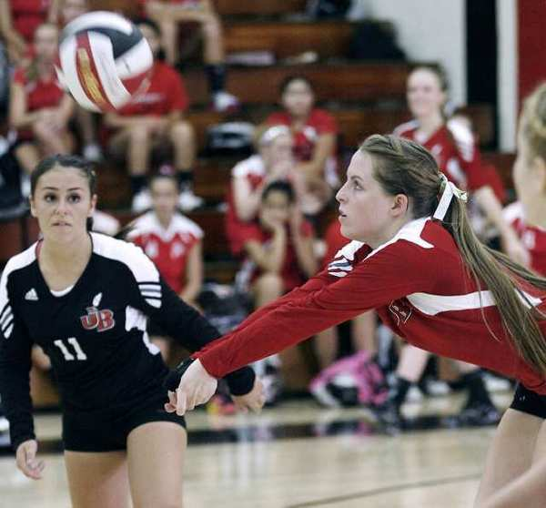 With Burroughs High School's Daniela Gonzalez, left, keeping a close eye on the action, Tori Adams digs the ball during a match with Glendale High.