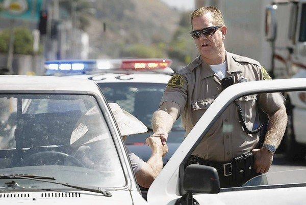 David Huelsen, a traffic detective with the L.A. County Sheriff's Department, interacts with a motorist on Pacific Coast Highway earlier this month. Huelsen is one of the lawmen that the Sheriff's Department has equipped with a digital camera in an effort to cut down on the number of innocent people jailed after being mistaken for wanted criminals.