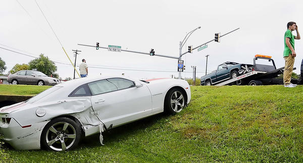 The driver of a Camaro that collided with a pickup truck at Broadfording Road and Salem Avenue in Hagerstown Tuesday scratches his head as the pickup is loaded onto a rollback truck while his car remains in a ditch.