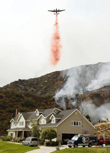 An airplane drops fire retardant on flames in the hills above La Cañada Flintridge in 2009. Slightly more than half of the homes at high risk from wildfire are in Southern California, a study found.