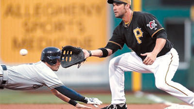 Milwaukee Brewers' Norichika Aoki, left, dives back safely to first as Pittsburgh Pirates first baseman Garrett Jones waits for the pick-off throw in the first inning of a baseball game in Pittsburgh on Tuesday.